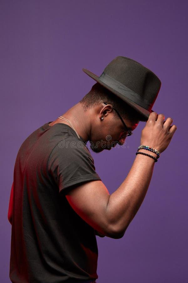 Dançarino masculino africano com dança do chapéu no t-shirt preto no fundo roxo fotografia de stock royalty free