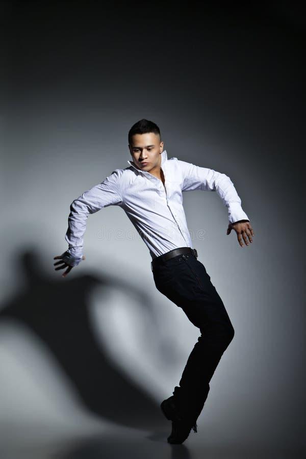 Dançarino moderno do estilo que levanta no fundo cinzento imagem de stock