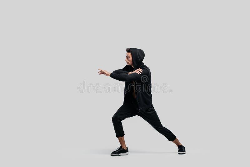 Dançarino novo considerável da dança da rua vestido em calças pretas, em uma camiseta em um torso despido e em danças de uma capa fotos de stock royalty free
