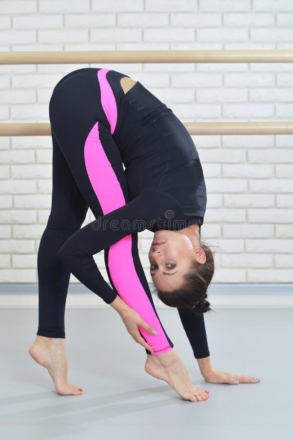 Dançarino novo da mulher elegante que estica no gym que está no dedo do pé Conceito da aptidão e do estilo de vida fotografia de stock royalty free