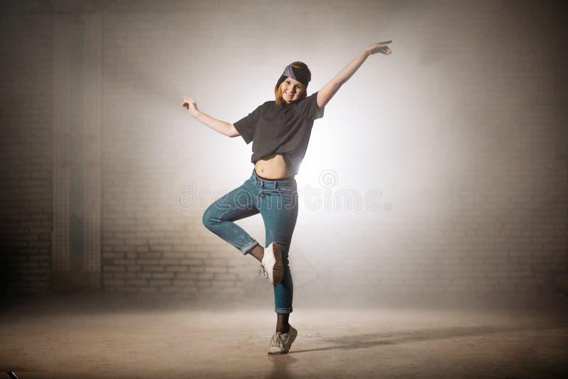 Dançarino novo da rua que executa o bailado fazendo movimentos do bailado imagem de stock royalty free