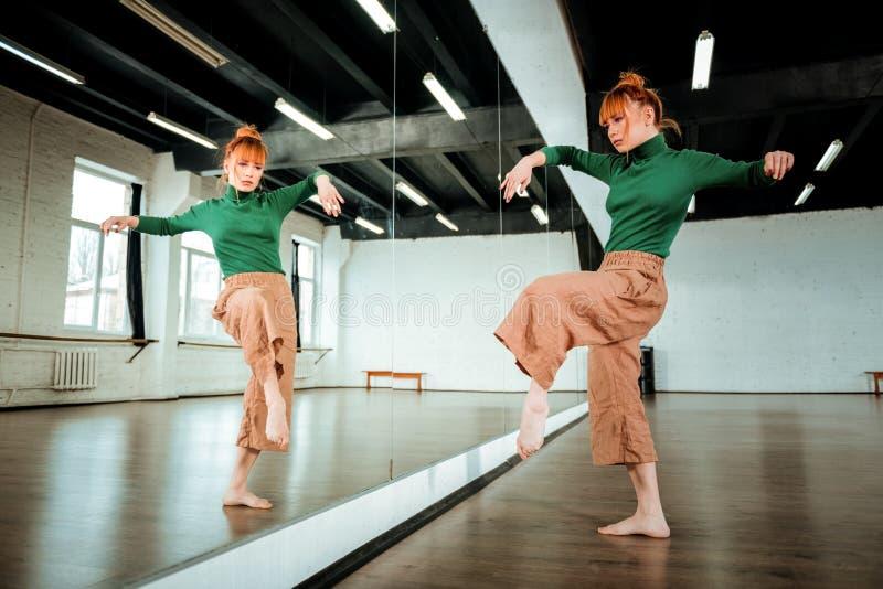 Dançarino profissional ruivo bonito em uma gola alta verde que olha séria imagem de stock
