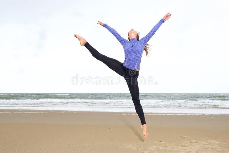 Dançarino que pula no ar na separação na praia imagens de stock royalty free