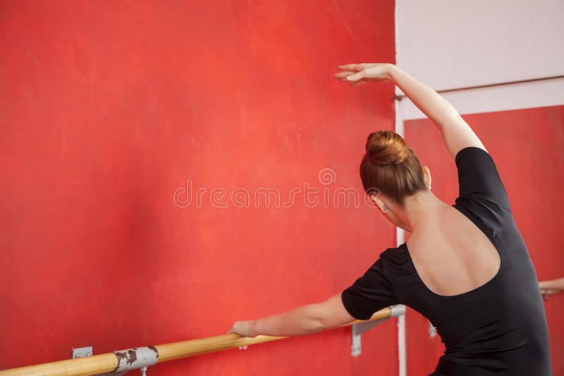 Dançarino Stretching At Barre In Ballet Studio imagem de stock royalty free