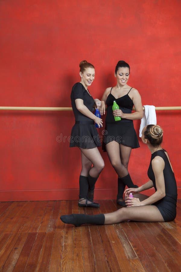 Dançarinos de bailado que guardam garrafas de água no estúdio imagem de stock royalty free