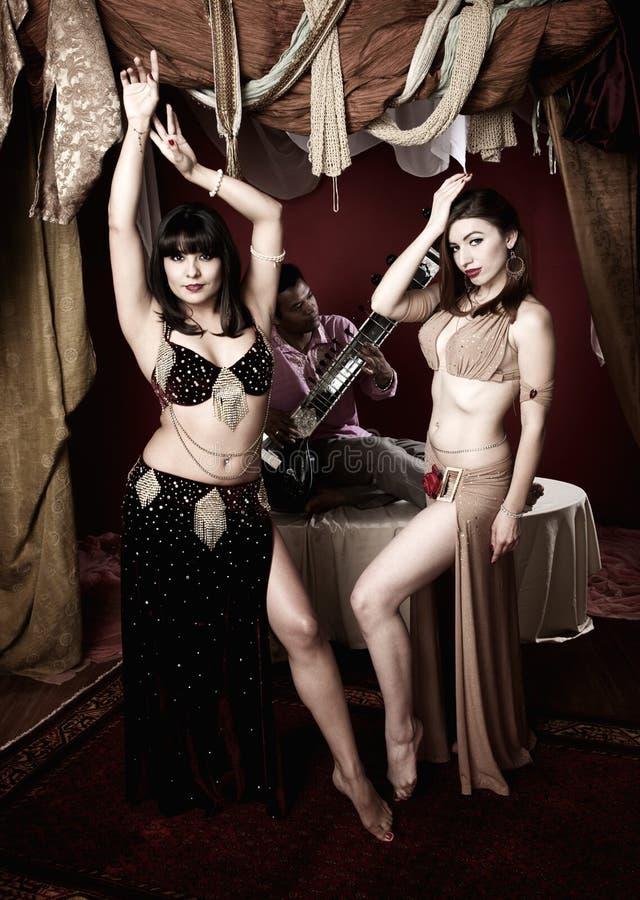 Dançarinos de barriga bonitos com o homem que joga o Sitar foto de stock