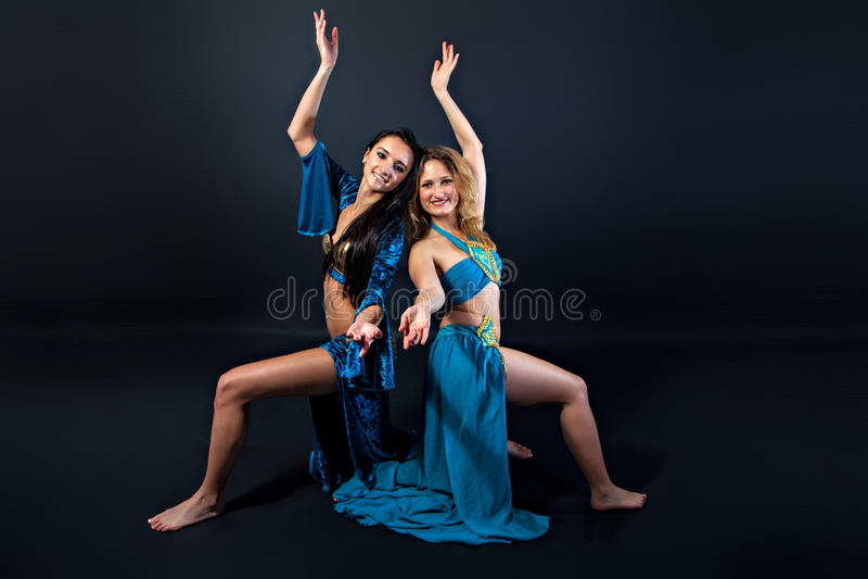Dançarinos de barriga bonitos novos em trajes azuis fotografia de stock