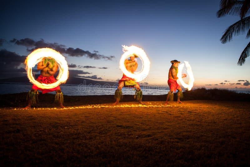 Dançarinos havaianos do incêndio no oceano imagens de stock