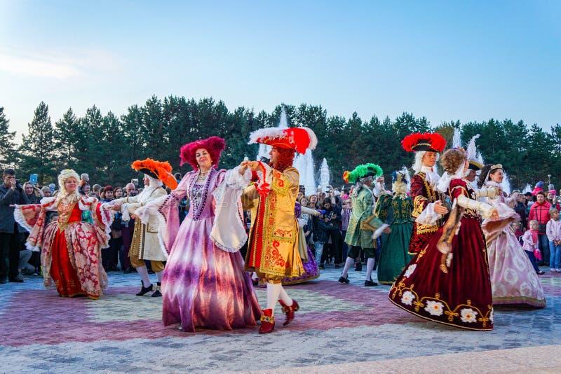 Dançarinos idosos nos trajes medievais históricos brilhantes, dançando no quadrado no verão imagens de stock