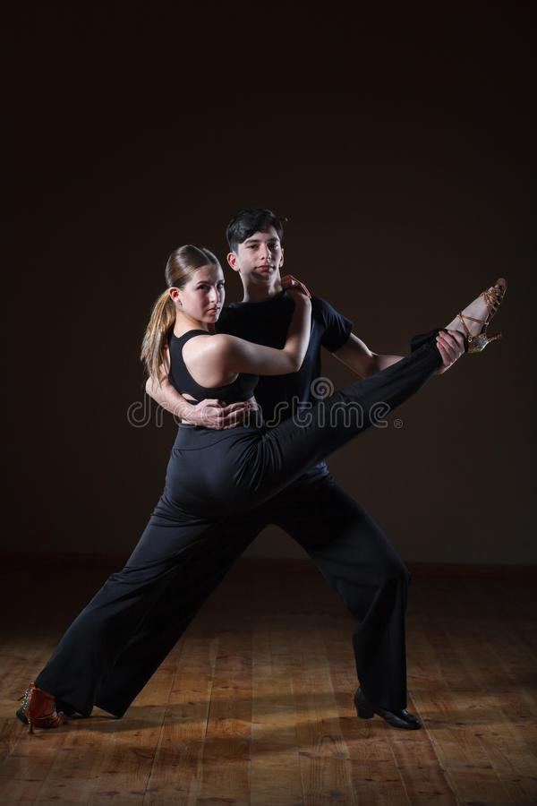 Dançarinos novos bonitos no salão de baile isolado no fundo preto fotos de stock royalty free