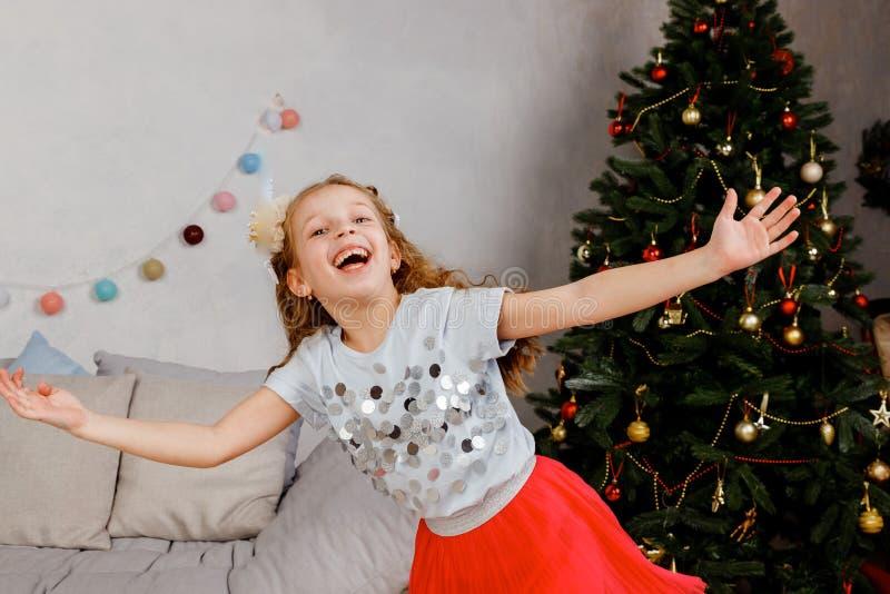 Danças bonitos da menina na noite do Natal A criança aprecia feriados de inverno Dançando, cantando, tendo o divertimento no foto de stock