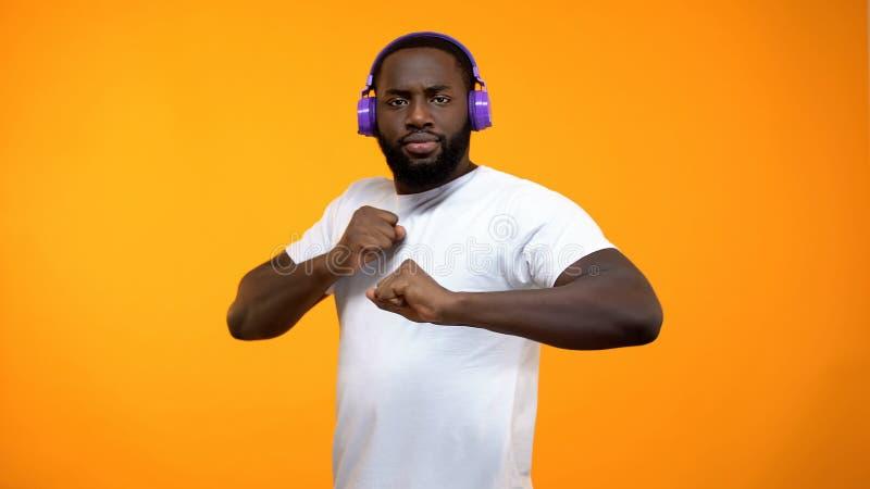 Dan?a afro-americana engra?ada nos fones de ouvido, desempenho do homem da mostra do talento, close-up fotografia de stock royalty free