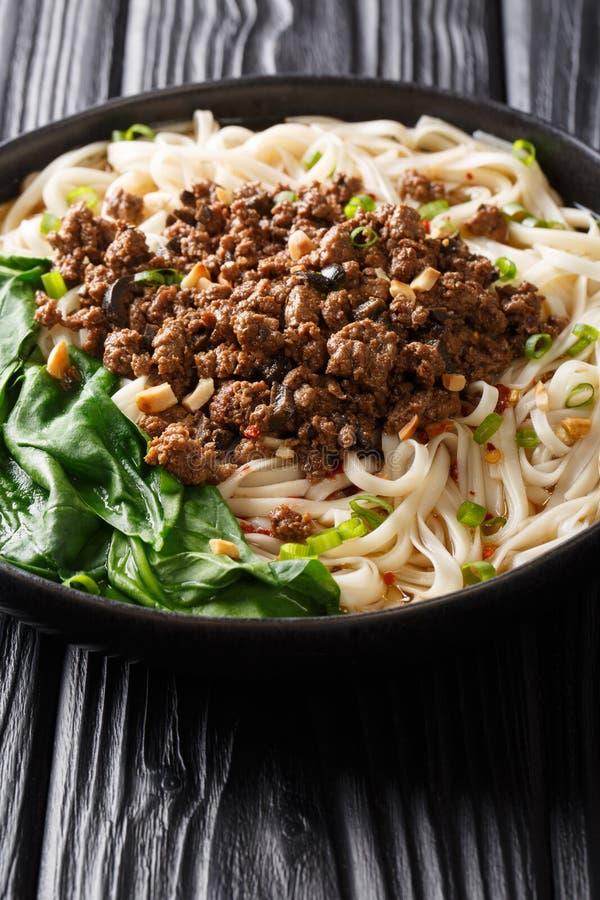 Dan Dan Noodles - savoureux et nouilles épicées de Sichuan servies avec le plan rapproché de viande hachée du plat vertical image libre de droits