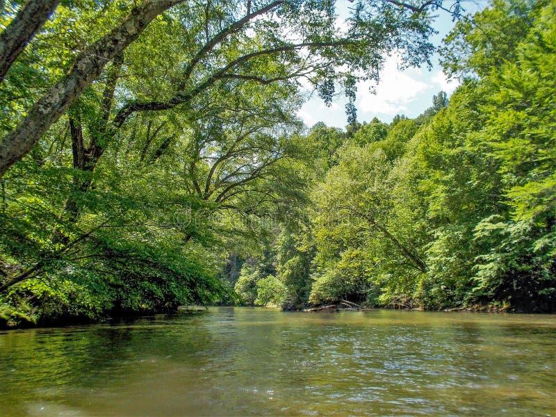Dan River Calm Water Reflections. Trees reflect on the calm, glassy surface of the Dan River near Danbury, North Carolina stock photo