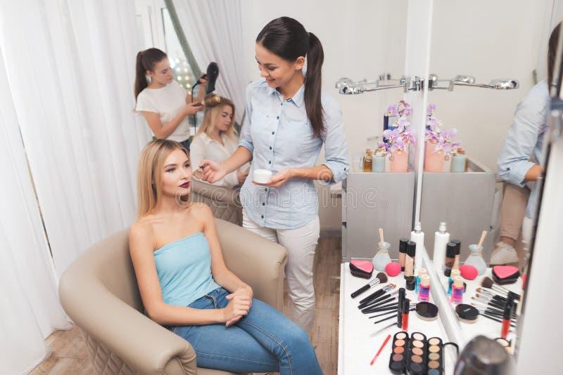 Dan una muchacha rubia maquillaje en un salón de belleza fotos de archivo