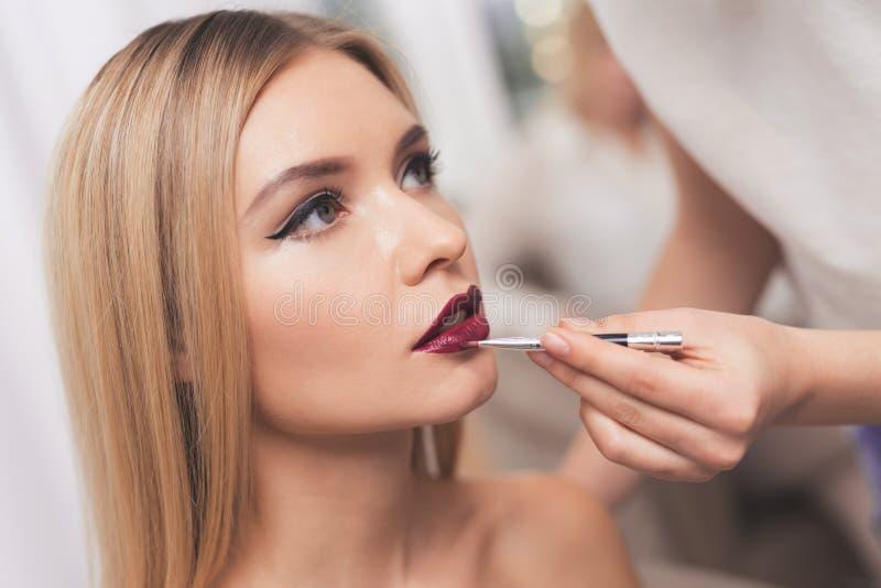 Dan una muchacha rubia maquillaje en un salón de belleza El visagiste teñe a la muchacha con los labios imagenes de archivo