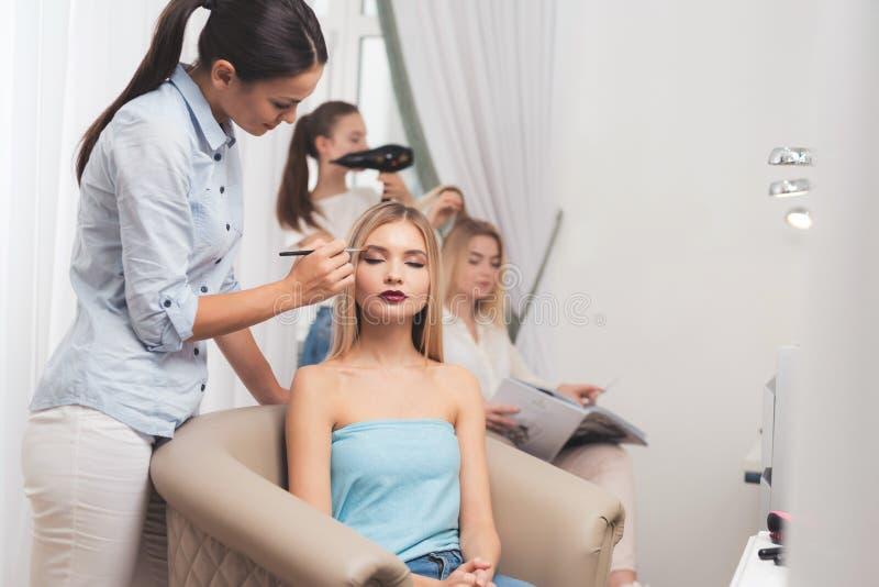 Dan una muchacha rubia maquillaje en un salón de belleza La muchacha está haciendo maquillaje con la aplicación de sombras de ojo imagen de archivo libre de regalías