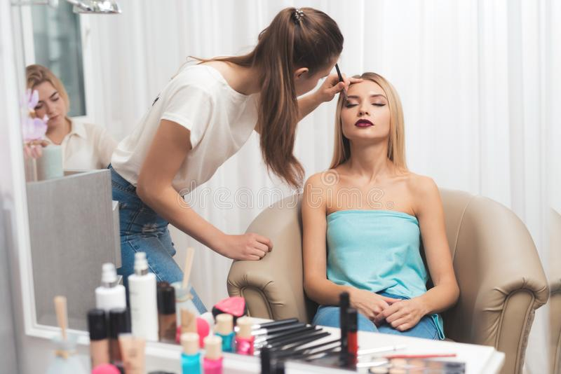 Dan una muchacha rubia maquillaje en un salón de belleza La muchacha está haciendo maquillaje con la aplicación de sombras de ojo imagen de archivo