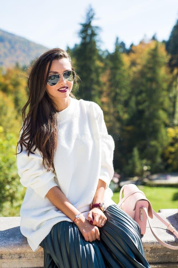 Dana bärande solglasögon för den härliga kvinnaståenden, den vita tröjan och den gröna kjolen royaltyfri bild
