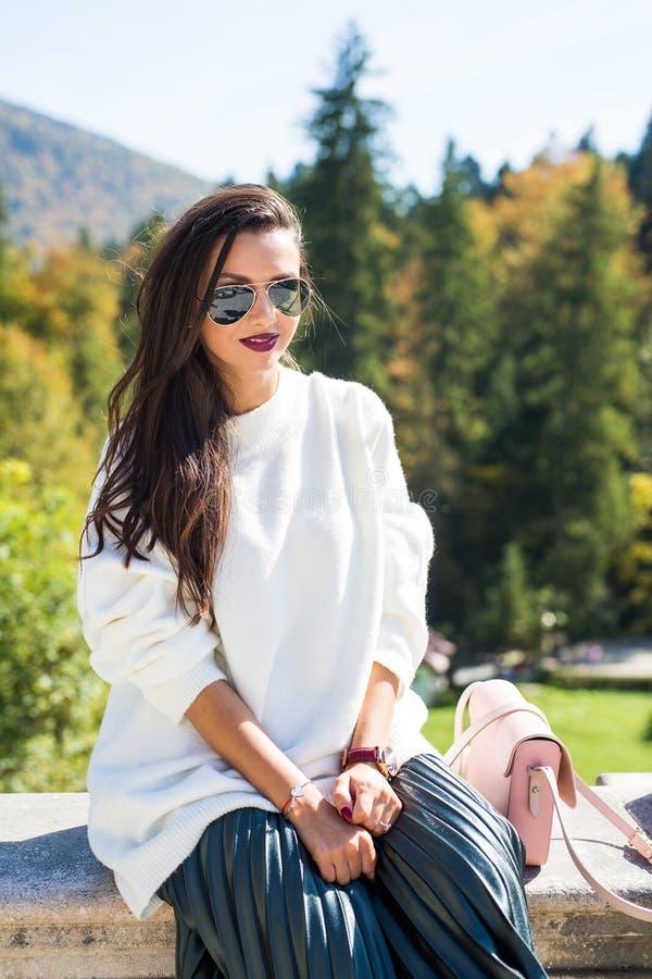 Dana bärande solglasögon för den härliga kvinnaståenden, den vita tröjan och den gröna kjolen arkivfoton