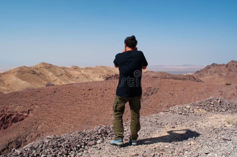 Dana Biosphere Reserve, Jordan, Middle East. Middle East, 03/10/2013: a man taking pictures of desertic landscape on the road that links the Dana Biosphere royalty free stock photo