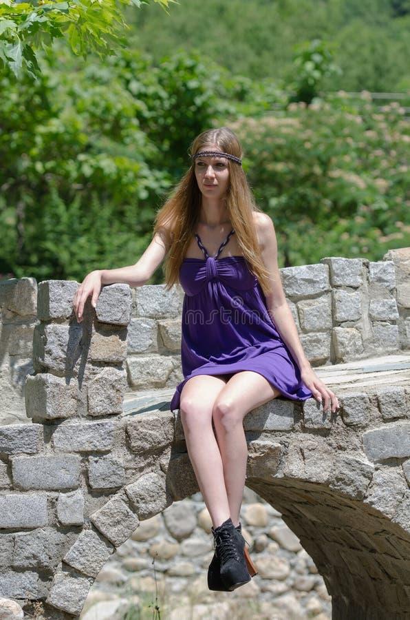 Dana blondinen med kort klänningsammanträde på den lilla stenbron arkivfoton