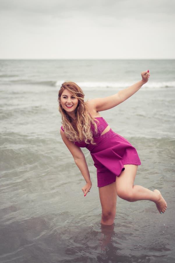 Dana blondinen på strandhavssidan som poserar skon-mindre i vatten arkivfoton