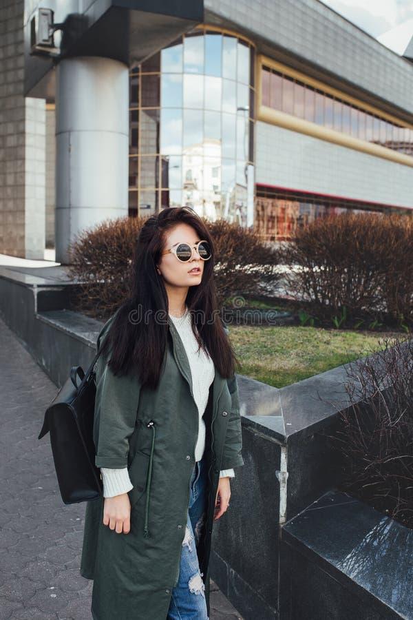 Dana closeupståenden av den trevliga nätta unga hipsterkvinnan som poserar i utomhus- solglasögon Lycklig flicka för brunett i gr arkivbild