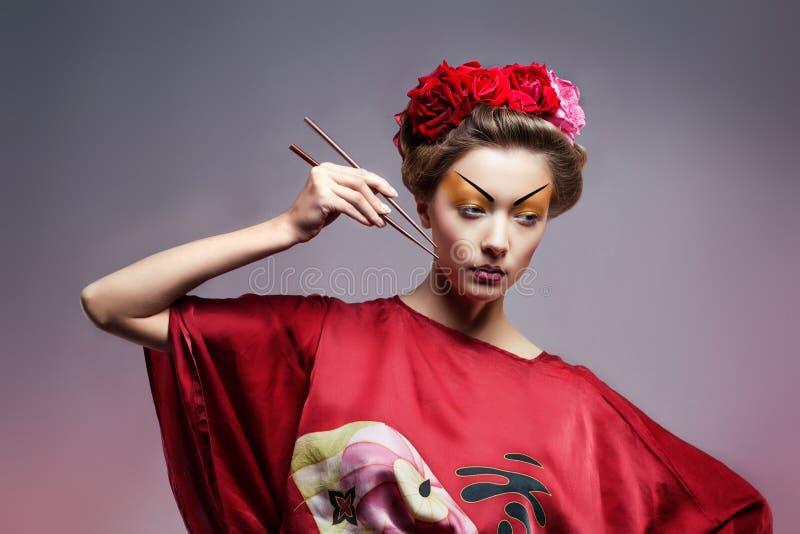 Dana den asiatiska kvinnan som ha på sig den traditionella japanska röda kimonoen    royaltyfria bilder