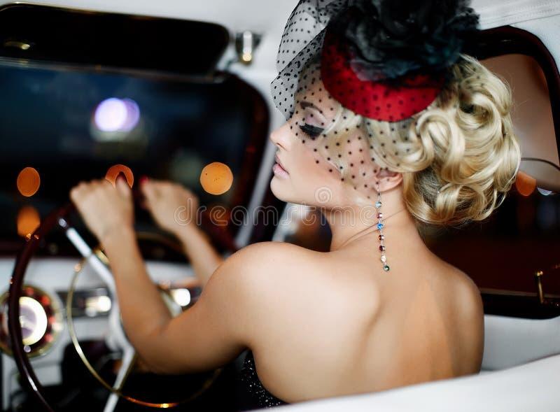 Dana den blonda modellen i retro stil i gammal bil arkivfoto