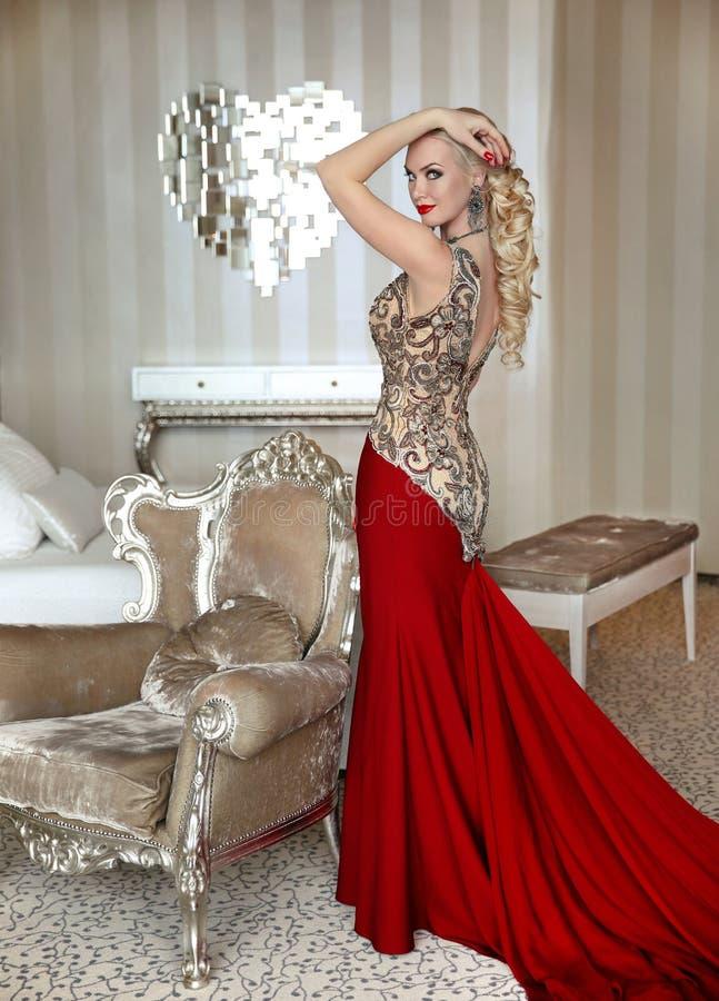 Dana den härliga blonda flickamodellen med den eleganta frisyren i rött arkivfoto
