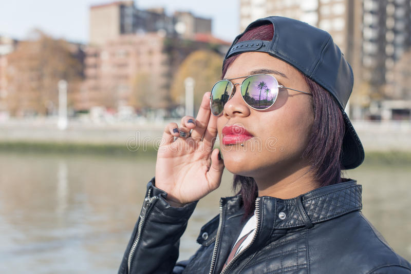 Dana den härliga latinska kvinnan med solglasögon och baseballmössan om den soliga dagen i gatan royaltyfria foton