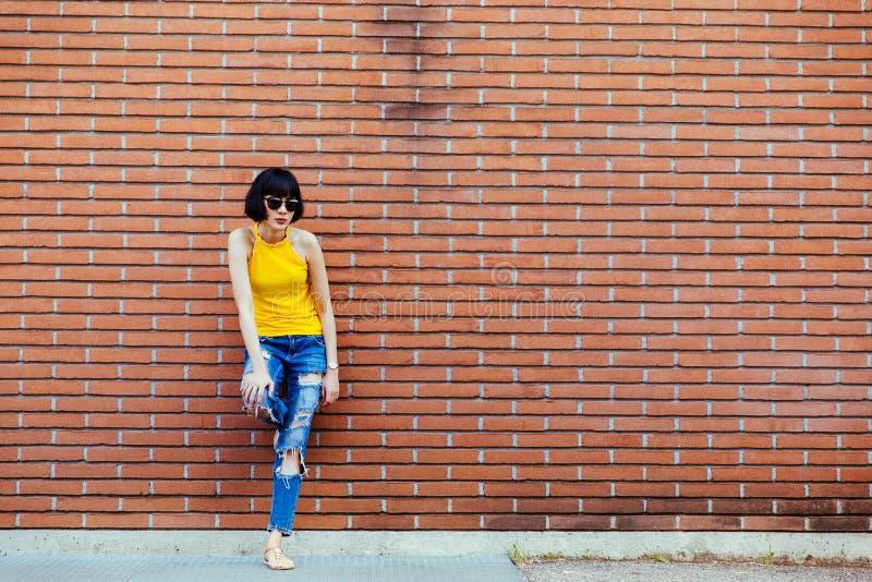 Dana den lyckliga le flickan för hipsteren coolt i solglasögon som poserar på tegelstenväggen royaltyfri fotografi