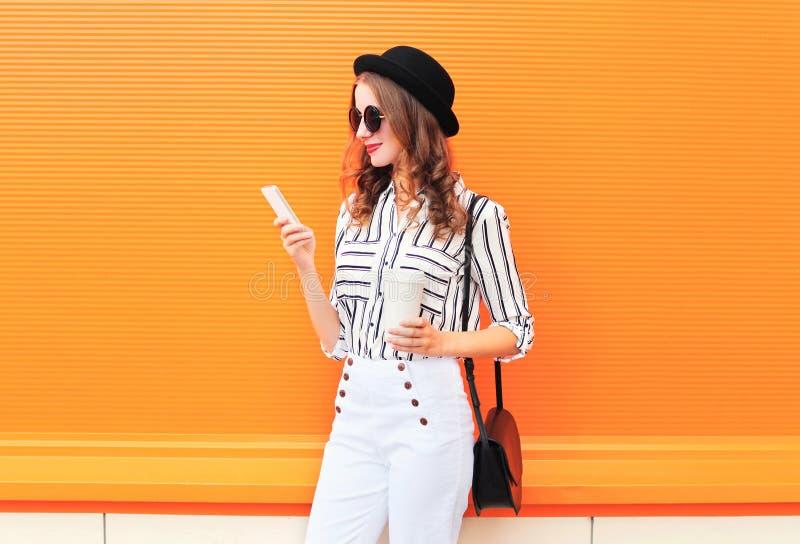 Dana den nätta modellen för den unga kvinnan genom att använda smartphonen med kaffekoppen som bär vita flåsanden för den svarta  royaltyfri foto