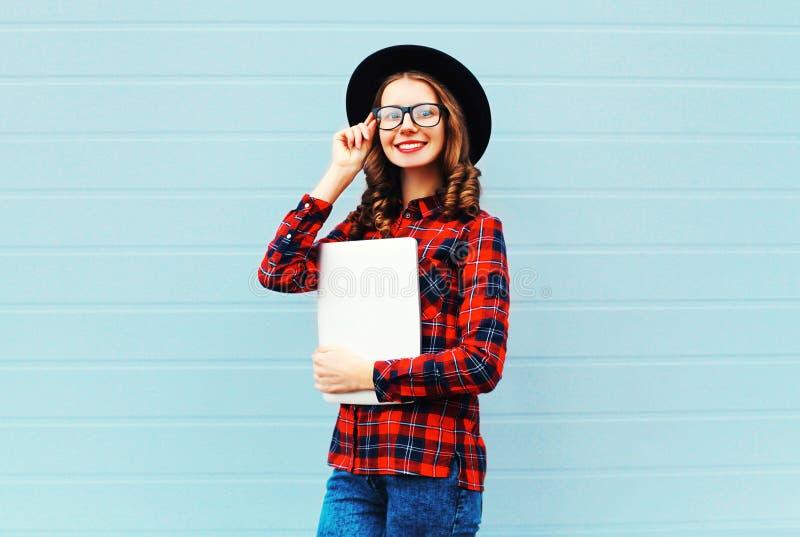 Dana den nätta unga le för den bärbar datordatoren eller minnestavlan för kvinna hållande PC:n i staden som bär en svart hatt, de royaltyfri fotografi