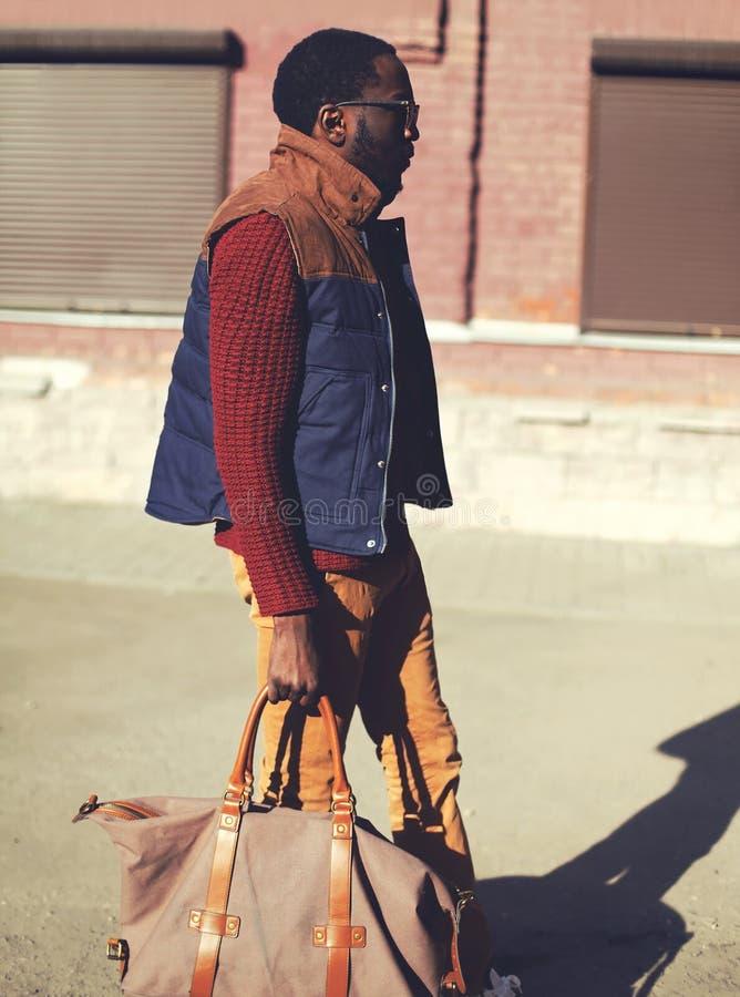 Dana den stiliga stilfulla afrikanska mannen som bär ett västomslag, tröja och påse som går i stad arkivbild