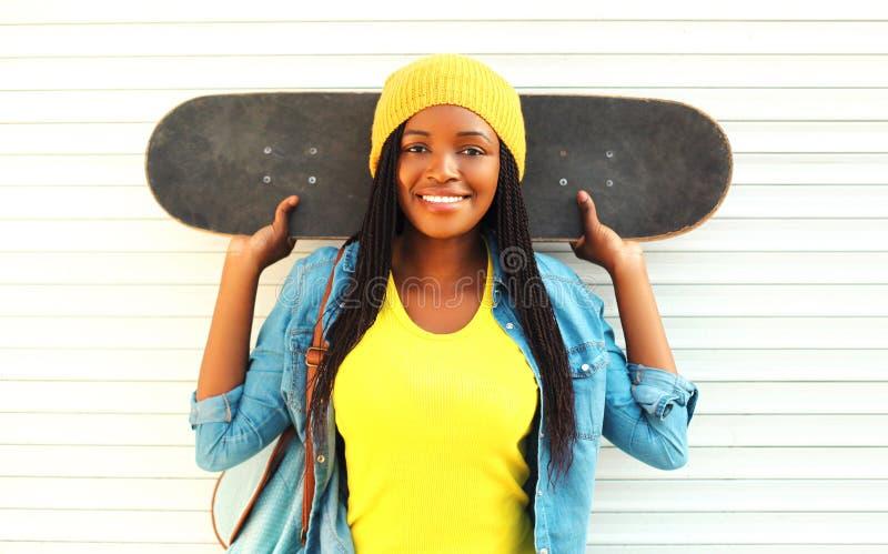 Dana den unga le afrikanska kvinnan för ståenden med skateboarden i färgrik kläder över vit arkivbild