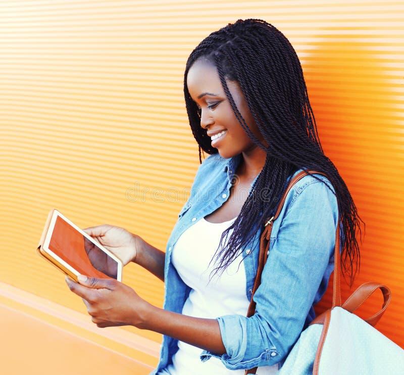 Dana den unga le afrikanska kvinnan som använder minnestavlaPC i staden över den färgrika apelsinen fotografering för bildbyråer