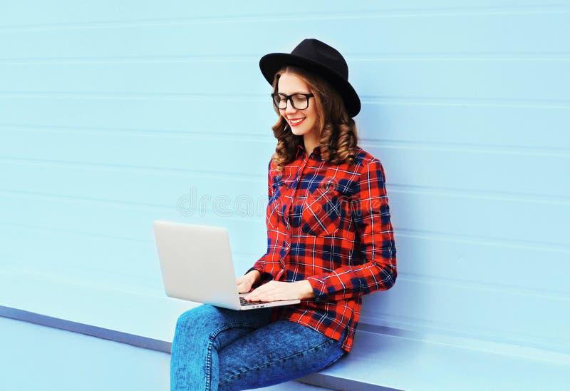 Dana den unga le kvinnan som arbetar genom att använda bärbar datordatoren utomhus i staden som bär en svart hatt, den röda rutig royaltyfri bild