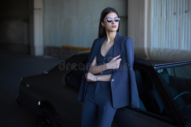 Dana flickaanseendet bredvid en retro sportbil på solen Stilfull kvinna i en blå dräkt och solglasögon som väntar nära den klassi royaltyfri fotografi