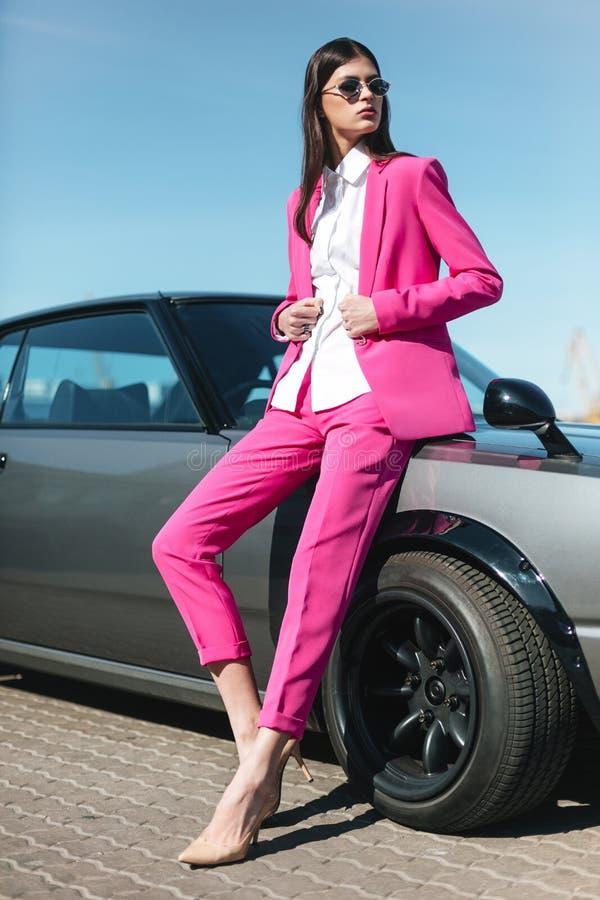 Dana flickaanseendet bredvid en retro sportbil på solen Stilfull kvinna i en rosa dräkt som väntar nära den klassiska bilen royaltyfri foto