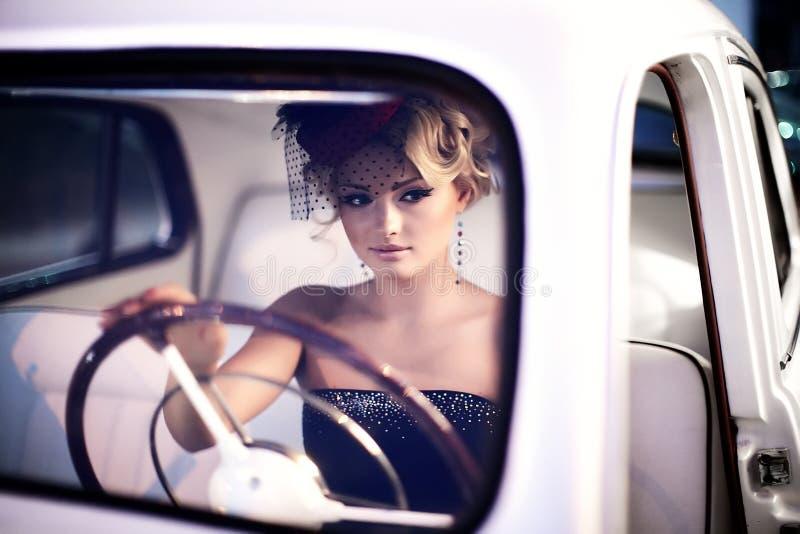 Dana flickan i retro stil som poserar nära den gamla bilen royaltyfri bild