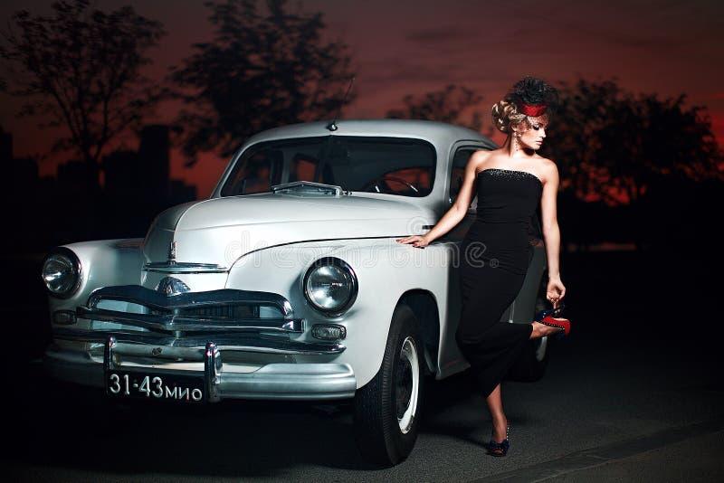 Dana flickan i retro stil som poserar nära den gamla bilen arkivfoton