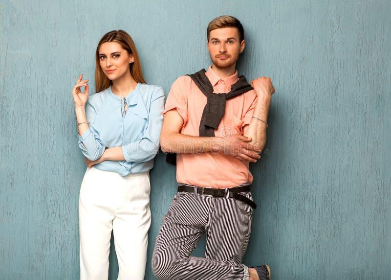 Dana flickan och grabben i uttagkläder som poserar på en blå backgro arkivbilder