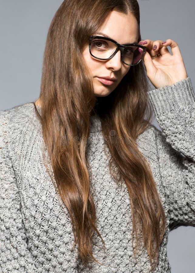Dana flickan på en grå bakgrund i studion som poserar med glas royaltyfria bilder