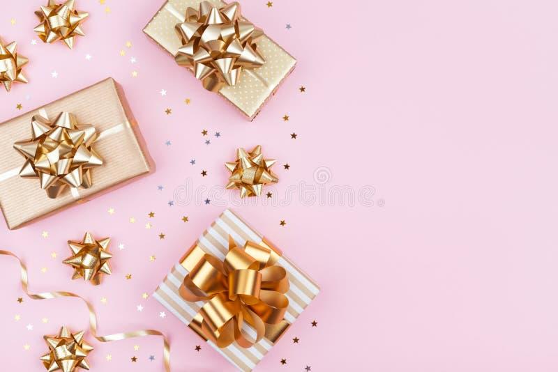 Dana gåvor eller gåvaaskar med guld- pilbågar och stjärnakonfettier på rosa bästa sikt för tabell Lägenhet som är lekmanna- för f royaltyfri bild