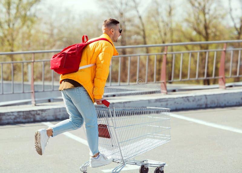 Dana grabben i solglasögon och ett hopp för gult omslag i en vagn för arkivfoton