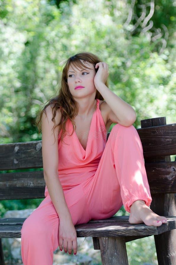 Dana kvinnan på bänken, med ett rosa styckplagg fotografering för bildbyråer
