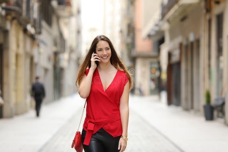 Dana kvinnan som går och talar på mobiltelefonen royaltyfri foto