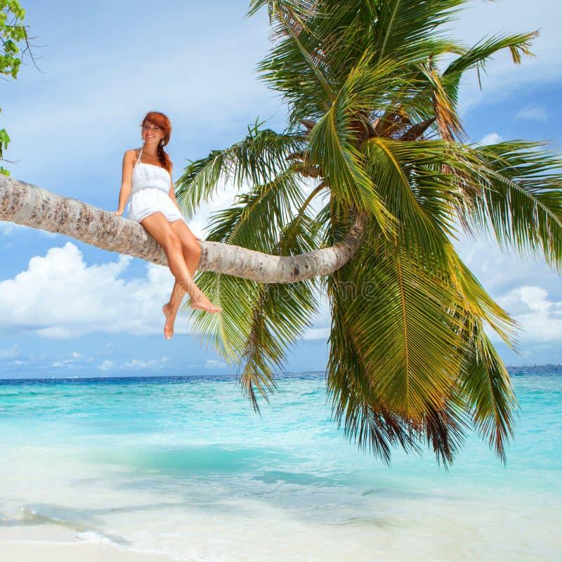Dana kvinnan som placerar på palmträdet på stranden royaltyfri fotografi